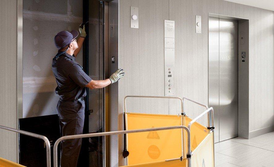 Service technician working on elevator door